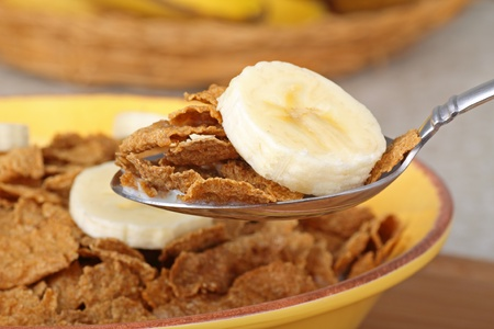 banana slice: Closeup of a spoonful of wheat flake cereal and banana slice