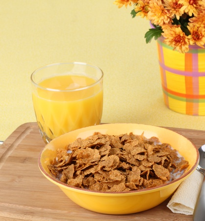 Breakfast wheat flake cereal with orange juice and flowers in background