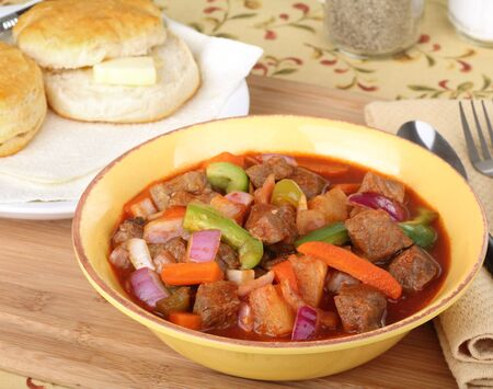 Bowl of beef stew with buttered biscuit in background