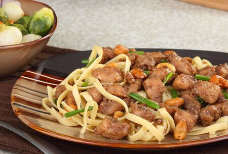 Chicken cashew with noodles on a dinner plate