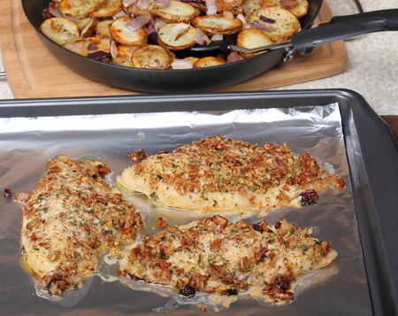 Catfish with cashew topping on a baking sheet with potatoes in background