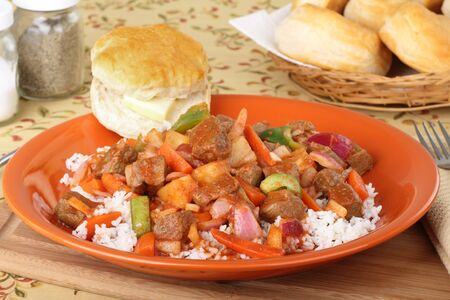 Sweet and sour beef stew on rice with a buttered biscuit Stock fotó