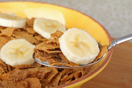 Closeup of a spoonful of bran flakes with a banana slice