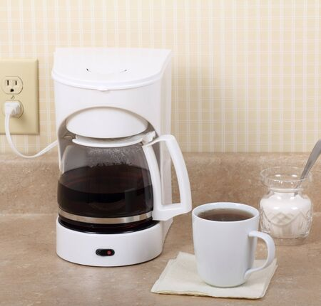 Coffee maker, cup of coffee and sugar bowl on kitchen counter Stock fotó