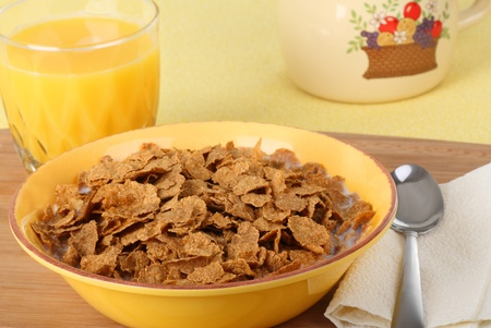 Bowl of wheat flake cereal and glass of orange juice Stok Fotoğraf