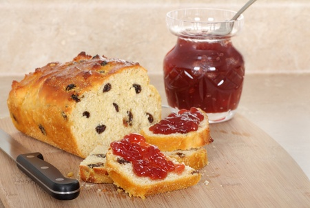 Raisin bread sliced on a cutting board with jam on the slices