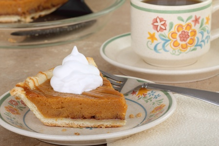 Slice of pumpkin pie with whipped cream and a cup of coffee photo