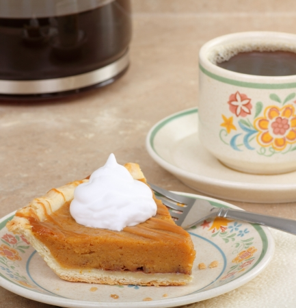 Slice of pumpkin pie topped with whipped cream and coffee photo