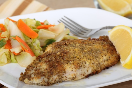 Closeup of a breaded catfish fillet with a lemon slice photo