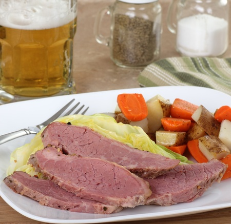 Sliced corned beef and cabbage with a glass of beer
