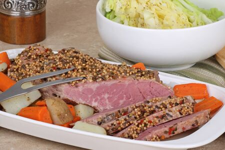 Corned beef with vegetables in a serving dish with cabbage in a bowl photo