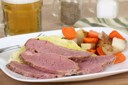 Slices of corned beef with cabbage and carrots and potatoes on a dinner plate photo