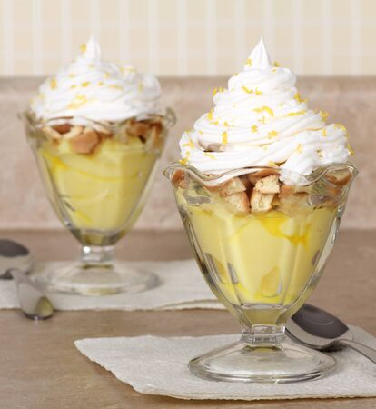 whipping: Lemon pudding with whipped cream in glass bowls
