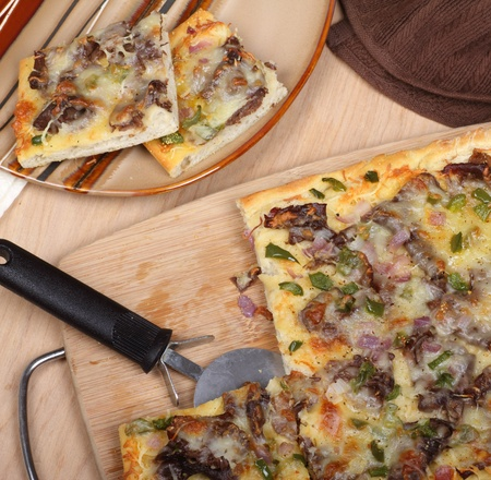 Sliced cheese steak pizza on a cutting board and plate