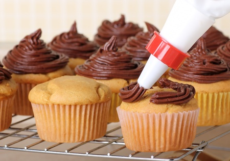 Piping chocolate frosting onto cup cakes on a wire rack