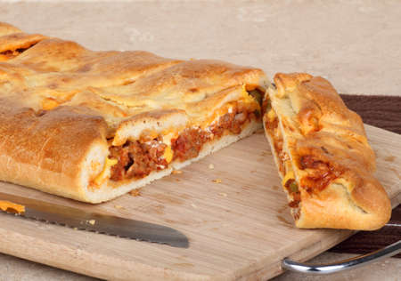 stromboli: Sliced stromboli with sausage and cheese on a cutting board Stock Photo