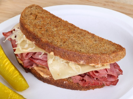 reuben: Grilled reuben sandwich with pastrami and swiss cheese on a plate