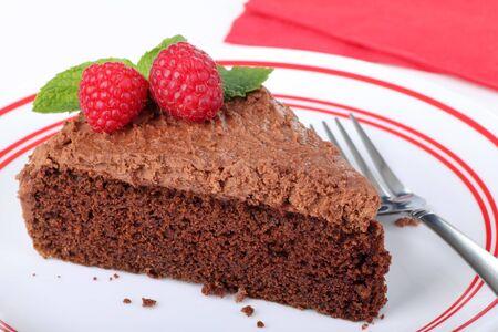 rebanada de pastel: Rebanada de pastel de chocolate con frambuesas y menta en un plato