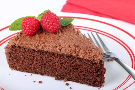 Slice of chocolate cake with raspberries and mint on a plate Stock Photo - 12955674