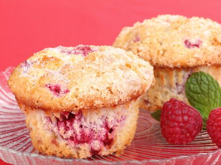Raspberry muffins on a glass plate with a red background
