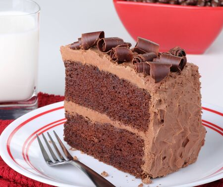 chocolate slice: Chocolate cake with chocolate curls and a glass of milk Stock Photo