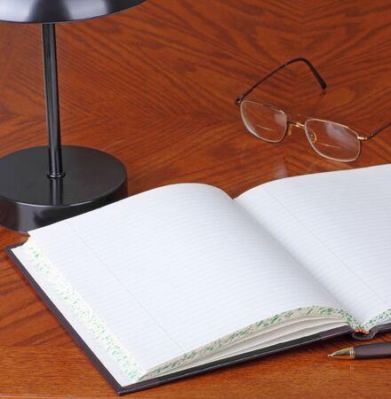 Leeg geopend logboek op een bureau met pen