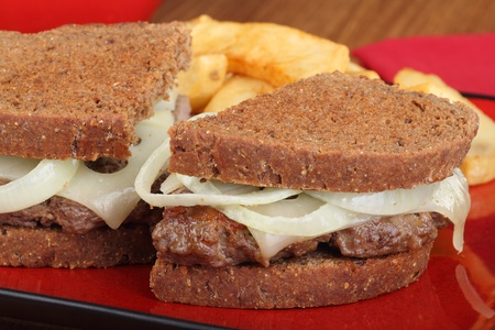 Closeup of a patty melt sandwich with cheese and onions