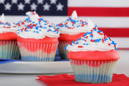 fourth july: Closeup of red white and blue cupcake with cupcakes and flag in background
