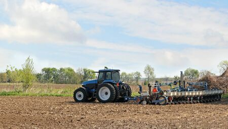 Blue tractor pulling a planter planting corn Stock Photo