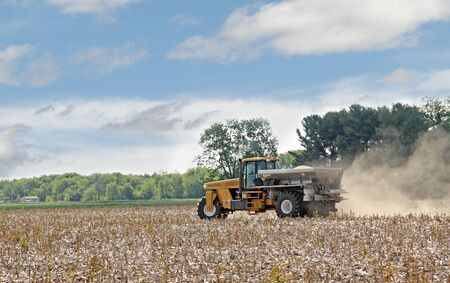 Vehicle spreading lime onto a farm field