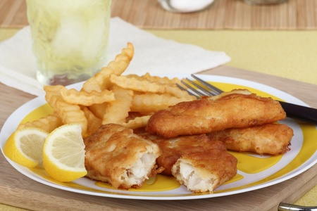 Battered fish fillet with french fries on a plate