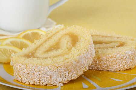 Two slices on lemon cake rolls on a plate