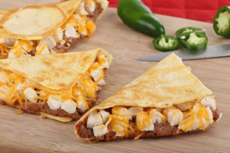 Chicken quesadill wedges with peppers in background on a cutting board photo