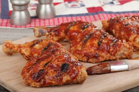 thighs: Bbq chicken quarters on a cutting board Stock Photo
