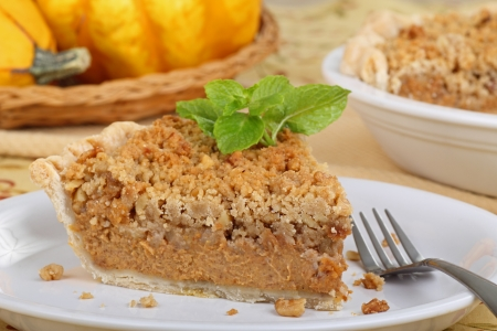 Slice of pumpkin streusel pie with mint leaves on a plate photo