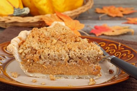 Slice of streusel pumpkin pie with autumn colors in background photo