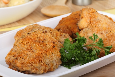 Breaded baked chicken thighs with parsley on a platter Banque d'images