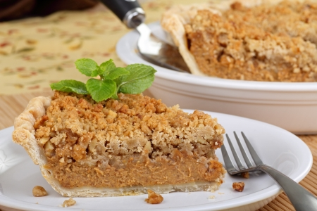 Slice of pumpkin streusel pie with mint leaves photo