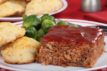 Closeup of slice of meatloaf with biscuits and brussels sprouts photo