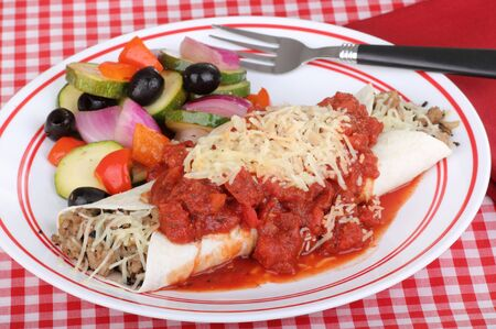 Sausage enchilada with cheese and tomato sauce on a plate