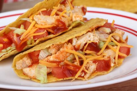 sause: Two tacos with chicken, tomato, lettuce, cheese and sause