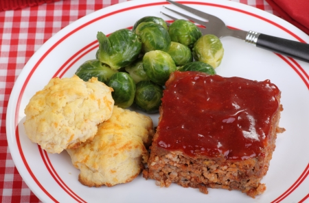 Top view of a meal of meatloaf, biscuits and brussels sprouts