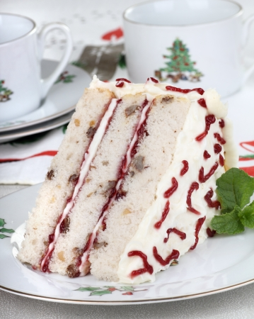 Slice of layer cake with Christmas cups in background photo