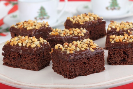 Brownies with chocolate nut frosting on a platter with Christmas cups in background Stock Photo - 16000137