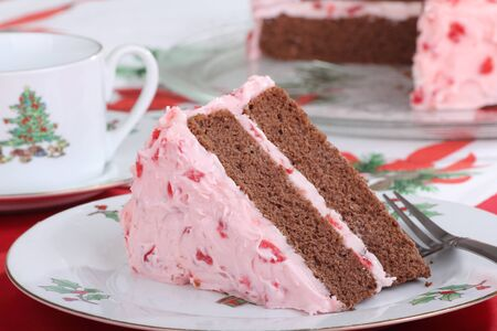 Piece of chocolate cake with cherry frosting on a Christmas plate Stock Photo - 16478899