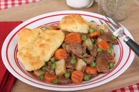 beef stew: Beef stew with carrots, peas and biscuits on a plate Stock Photo