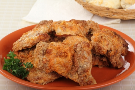 Orange plate of breaded baked chicken thighs Stock Photo - 17004586