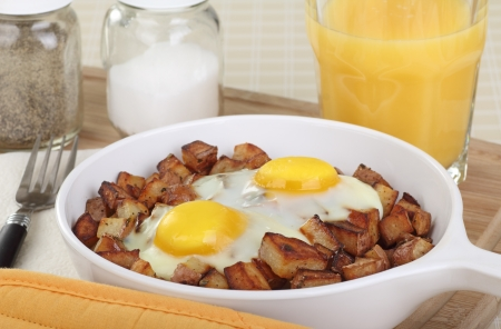 Sunny side up fried eggs on top of fried potatoes