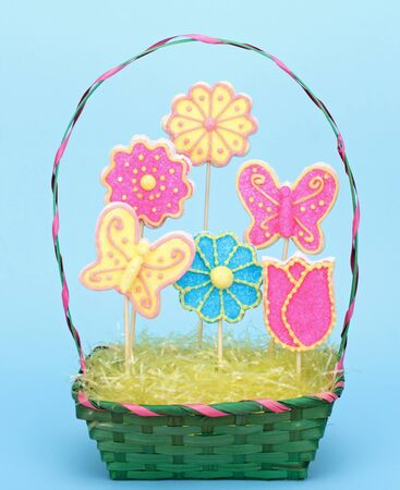 Sugar cookies shaped as flowers and butterflies in a green easter basket with blue background Stock Photo - 17374615