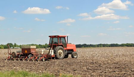 Tractor planting a crop in a farm field
